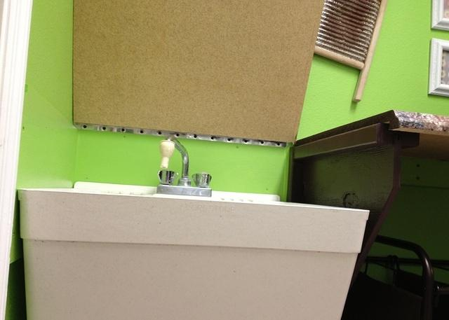 Laundry folding countertop hinges open to reveal utility sink 4